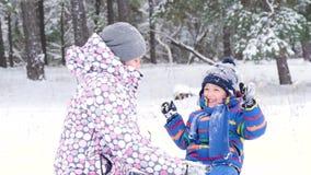 Μια ευτυχή μητέρα και ένα παιδικό παιχνίδι στο χιόνι, ρίχνοντας το στη κάμερα, καθμένος ενάντια σε ένα χειμερινό δάσος ή ένα πάρκ φιλμ μικρού μήκους