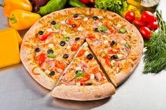 Μια εύγευστη ιταλική πίτσα με το μπέϊκον, τις ελιές και το τυρί με το ομοιόμορφα κομμένο κομμάτι Στοκ Εικόνες