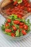 Μια εύγευστη σαλάτα με Arugula, ντομάτες κερασιών στο κύπελλο γυαλιού Τρόφιμα που προετοιμάζονται στον πίνακα κουζινών Κάθετη εικ Στοκ φωτογραφία με δικαίωμα ελεύθερης χρήσης