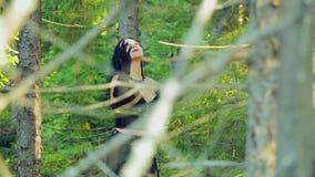 Μια εύθυμη μάγισσα στις μαύρες περιστροφές ενδυμάτων γύρω στο χορό στις δασικές αποκριές Ύφος Gothick απόθεμα βίντεο