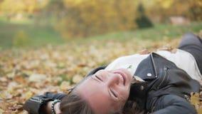 Μια εύθυμη νέα γυναίκα βρίσκεται στα πεσμένα κίτρινα φύλλα απόθεμα βίντεο