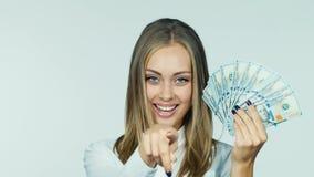 Μια ελκυστική γυναίκα με έναν ανεμιστήρα των δολαρίων απόθεμα βίντεο