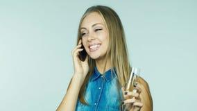 Μια ελκυστική γυναίκα με ένα ποτήρι της σαμπάνιας που λαμβάνει τα συγχαρητήρια τηλεφωνικώς απόθεμα βίντεο