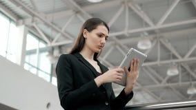 Μια ελκυστική νέα γυναίκα στέκεται μπροστά από τη κάμερα με το PC ταμπλετών, μέσος πυροβολισμός της επιχειρησιακής γυναίκας στο π απόθεμα βίντεο