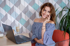 Μια ελκυστική νέα επιχειρηματίας που χρησιμοποιεί το τηλέφωνο και το lap-top της σε έναν καφέ Στοκ Φωτογραφία