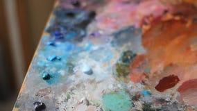 Μια ζωηρόχρωμη παλέτα του ελαιοχρώματος σε έναν πίνακα κοντραπλακέ Το χέρι συμπιέζει το ακρυλικό χρώμα από έναν σωλήνα απόθεμα βίντεο