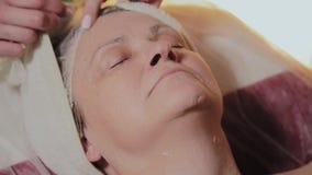 Μια ηλικιωμένη γυναίκα αναμένει την έναρξη της διαδικασίας στο σαλόνι ομορφιάς απόθεμα βίντεο