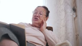 Μια ηλικιωμένη γυναίκα απολαμβάνει σε μια καρέκλα και μεγαλοφώνως στο υπόβαθρο του παραθύρου κλείστε επάνω φιλμ μικρού μήκους