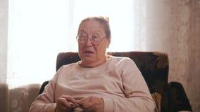 Μια ηλικιωμένη γυναίκα απολαμβάνει σε μια πολυθρόνα και στο υπόβαθρο του παραθύρου απόθεμα βίντεο