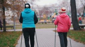 Μια ηλικιωμένη γυναίκα δίνει το σήμα χεριών και δύο ηλικιωμένες γυναίκες αρχίζουν στα ραβδιά του σκανδιναβικού περπατήματος απόθεμα βίντεο