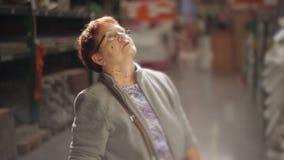 Μια ηλικιωμένη γυναίκα επιλέγει μια σκάλα στην υπεραγορά κατασκευής σπιτιών φιλμ μικρού μήκους