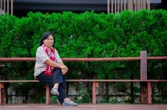 Μια ηλικιωμένη γυναίκα κάθεται σε ένα δημόσιο πάρκο στοκ φωτογραφίες