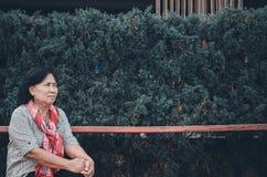 Μια ηλικιωμένη γυναίκα κάθεται σε ένα δημόσιο πάρκο στοκ εικόνα με δικαίωμα ελεύθερης χρήσης