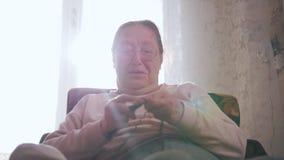 Μια ηλικιωμένη γυναίκα κάθεται σε μια καρέκλα και πλέκει στο υπόβαθρο του παραθύρου απόθεμα βίντεο