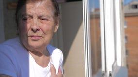 Μια ηλικιωμένη γυναίκα κοιτάζει από το παράθυρο απόθεμα βίντεο