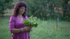 Μια ηλικιωμένη γυναίκα κρατά μια ανθοδέσμη Wildflowers και των χλοών και βλέπει ένα σμήνο Midges στροβιλιμένος επάνω από την ανθο απόθεμα βίντεο