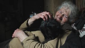Μια ηλικιωμένη γυναίκα με την γκρίζα τρίχα κρατά τη μαύρη γάτα της στα όπλα της, παίζει με την, χαμόγελα, ζωές σε ένα εγκαταλειμμ