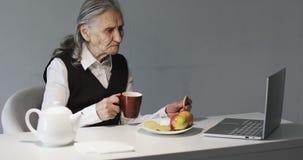 Μια ηλικιωμένη γυναίκα με τις βαθιές ρυτίδες έχει το πρόγευμα στο γραφείο και εξετάζει το lap-top απόθεμα βίντεο