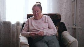 Μια ηλικιωμένη γυναίκα μιλά καθμένος σε μια καρέκλα και πλέκοντας στο υπόβαθρο του παραθύρου κλείστε επάνω απόθεμα βίντεο