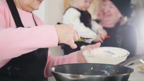 Μια ηλικιωμένη γυναίκα που κατασκευάζει τις τηγανίτες στη φωτεινή κουζίνα Βάλτε τη ζύμη στο τηγάνι Μια άλλη ηλικιωμένη γυναίκα πο απόθεμα βίντεο
