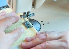 Μια ηλικιωμένη γυναίκα ράβει σε μια γραφομηχανή Στοκ Εικόνες