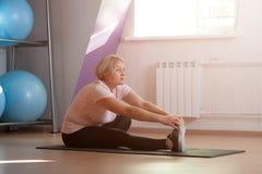 Μια ηλικιωμένη γυναίκα συμμετέχει στο τέντωμα στη γυμναστική στοκ φωτογραφίες με δικαίωμα ελεύθερης χρήσης