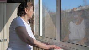 Μια ηλικιωμένη γυναίκα υπερασπίζεται το παράθυρο και κοιτάζει έξω στον ηλιόλουστο καιρό απόθεμα βίντεο
