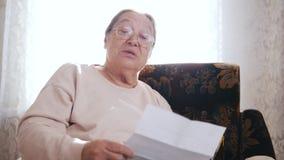 Μια ηλικιωμένη επιστολή ανάγνωσης γυναικών μεγαλοφώνως καθμένος σε μια καρέκλα στο υπόβαθρο του παραθύρου φιλμ μικρού μήκους
