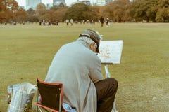 Μια ηλικιωμένη ιαπωνική συνεδρίαση ατόμων σε μια καρέκλα και σχέδιο το τοπίο σε έναν καμβά στοκ εικόνες