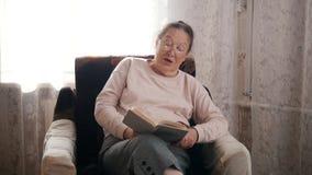 Μια ηλικιωμένη συνεδρίαση γυναικών σε μια καρέκλα και ανάγνωση μεγαλοφώνως στο υπόβαθρο του παραθύρου στοκ φωτογραφία