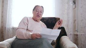 Μια ηλικιωμένη συνεδρίαση γυναικών σε μια καρέκλα και μια επιστολή ανάγνωσης μεγαλοφώνως στο υπόβαθρο του παραθύρου απόθεμα βίντεο