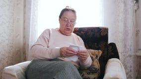 Μια ηλικιωμένη συνεδρίαση γυναικών σε μια καρέκλα και κρατά το έγγραφο στα χέρια στο υπόβαθρο του παραθύρου απόθεμα βίντεο