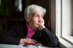 Μια ηλικιωμένη γυναίκα που φαίνεται δυστυχώς έξω το παράθυρο στοκ εικόνα
