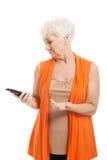 Μια ηλικιωμένη κυρία που χρησιμοποιεί το κινητό τηλέφωνο. στοκ φωτογραφίες