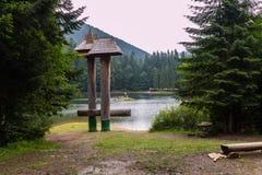 Μια θέση που χαλαρώνει στην ακτή μιας λίμνης βουνών με έναν πάγκο και ένα ενδιαφέρον γλυπτό φιαγμένους από ξύλο Στοκ Εικόνες