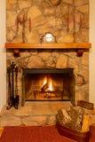 Μια θερμή πυρκαγιά σε μια όμορφη εστία πετρών με το ρολόι και candelabras στο μανδύα στοκ εικόνα με δικαίωμα ελεύθερης χρήσης