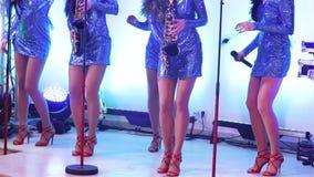Μια θηλυκή ζώνη μουσικής αποδίδει στη σκηνή, όμορφα κορίτσια με τα saxophones στη σκηνή Saxophone παιχνιδιού κοριτσιών, όμορφο απόθεμα βίντεο