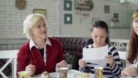 Μια θηλυκή ομάδα κάθεται σε έναν καφέ για ένα φλυτζάνι του τσαγιού Οι συνάδελφοι επικοινωνούν στα διαφορετικά θέματα κατά τη διάρ απόθεμα βίντεο