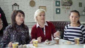 Μια θηλυκή ομάδα κάθεται σε έναν καφέ για ένα φλυτζάνι του τσαγιού Οι συνάδελφοι επικοινωνούν στα διαφορετικά θέματα κατά τη διάρ φιλμ μικρού μήκους