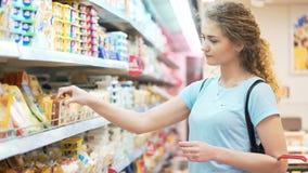Μια θηλυκή κυρία ψάχνει την ποικιλία του τυριού απόθεμα βίντεο