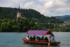 Μια ισχυρή αρσενική βάρκα rower απολαμβάνει μια βάρκα για τους τουρίστες στη λίμνη που αιμορραγείται με την πολύ ζωηρόχρωμη κάλυψ Στοκ Φωτογραφία