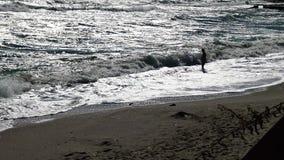 Μια ισχυρή θύελλα εν πλω, κύματα και άσπρος αφρός που κυλούν στην αμμώδη παραλία απόθεμα βίντεο