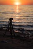 Μια κάμερα σε ένα τρίποδο που παίρνει τις εικόνες για ένα timelapse στην παραλία Στοκ Εικόνες