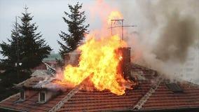 Μια καίγοντας κορυφή στεγών σπιτιών