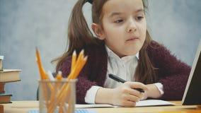 Μια καλή μαθήτρια κάθεται στον πίνακα σε ένα γκρίζο υπόβαθρο Κατά τη διάρκεια αυτού του γραψίματος, χαμόγελα χορού εργασίας Αργές απόθεμα βίντεο