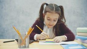 Μια καλή μαθήτρια κάθεται στον πίνακα σε ένα γκρίζο υπόβαθρο Κατά τη διάρκεια αυτού, η αυτοκόλλητη ετικέττα παίρνει σε ένα κίτριν φιλμ μικρού μήκους