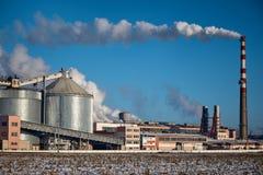 Μια καπνοδόχος εκπέμπει τον καπνό - ο σαφής μπλε ουρανός στο υπόβαθρο στοκ εικόνα
