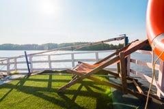 Μια καρέκλα παραλιών στο πεζούλι βαρκών για κάνει ηλιοθεραπεία τη μεσημβρία στοκ φωτογραφία με δικαίωμα ελεύθερης χρήσης
