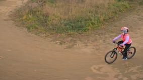 Μια καυκάσια οδική διαδρομή ποδηλάτων γύρων παιδιών στο πάρκο ρύπου Κορίτσι που οδηγά το μαύρο πορτοκαλή κύκλο στη πίστα αγώνων Τ απόθεμα βίντεο