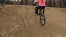 Μια καυκάσια οδική διαδρομή ποδηλάτων γύρων παιδιών στο πάρκο ρύπου Κορίτσι που οδηγά το μαύρο πορτοκαλή κύκλο στη πίστα αγώνων Τ φιλμ μικρού μήκους